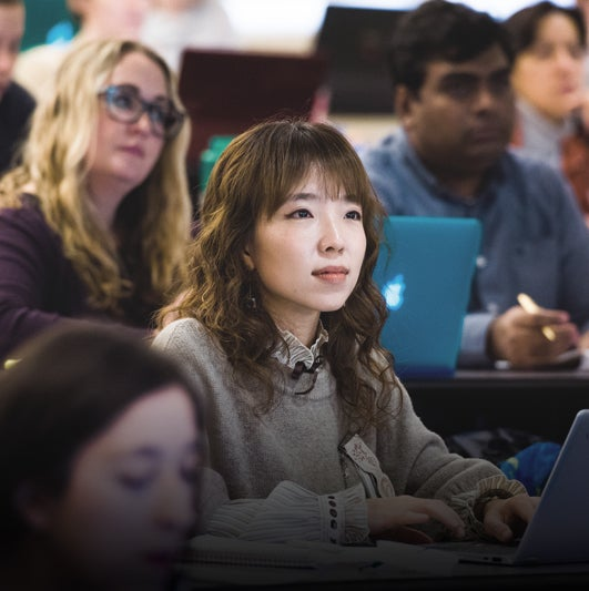 Focused shot of a young woman included in a group of students taking notes in a lecture hall