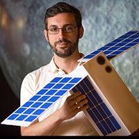 Craig Hardgrove holding the shoebox-sized satellite CubeSat.